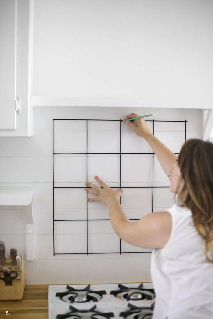 """Mandi marks the corners where the support hooks will go. She notes: """"If you don't have horizontal lines to use as a guide, as I did, thanks to my paneling, you may need someone to hold up a level to make sure it's straight."""""""