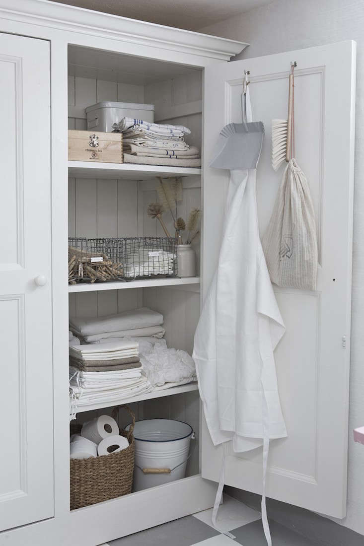 Linen closet meets utility room in an armoire photographed by Mari Eriksson ofAn Angel at My Table.