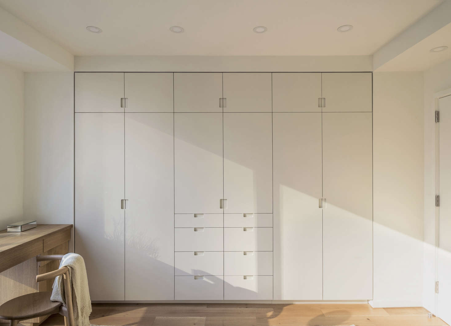 In a workstead designed bedroom built in closets feature painted millwork with flush