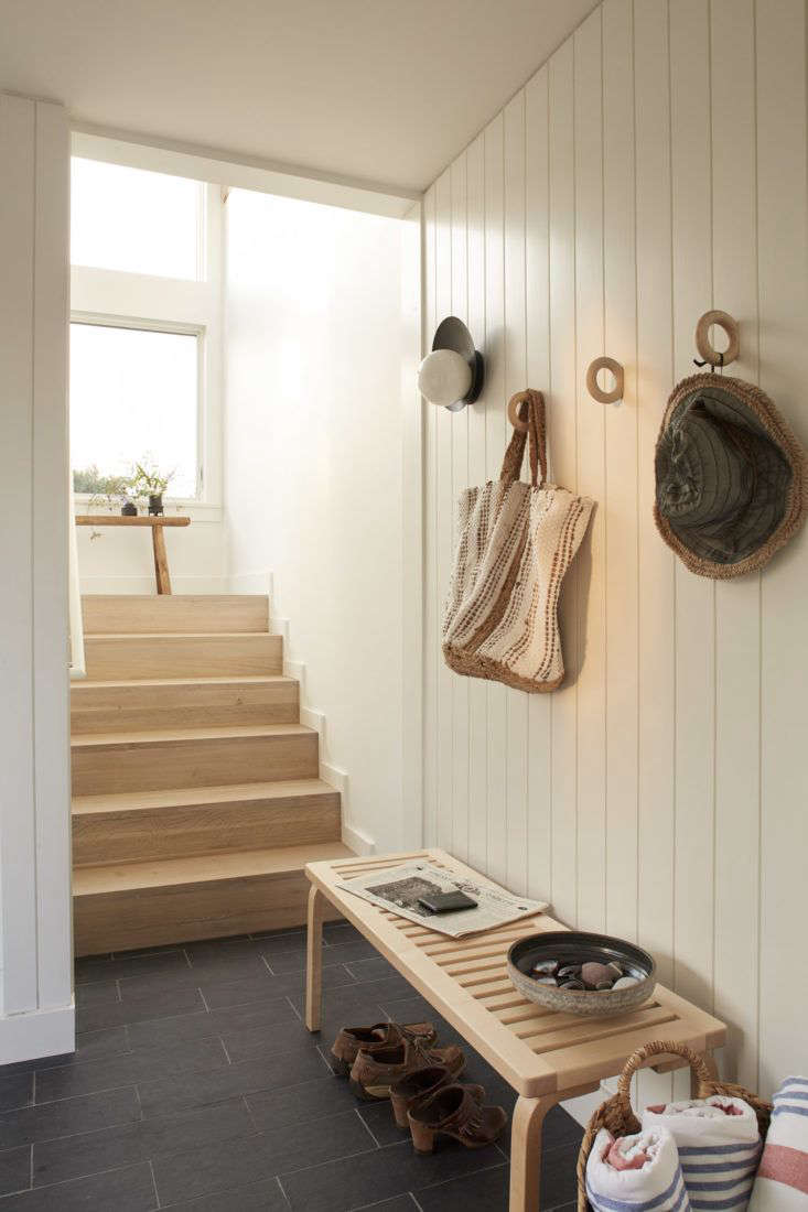 The simple entryway, located on the ground floor of the cottage, has a bench for tying shoes, a seagrass basket to store towels, and a series of Danish wood hooks to hold accoutrements.