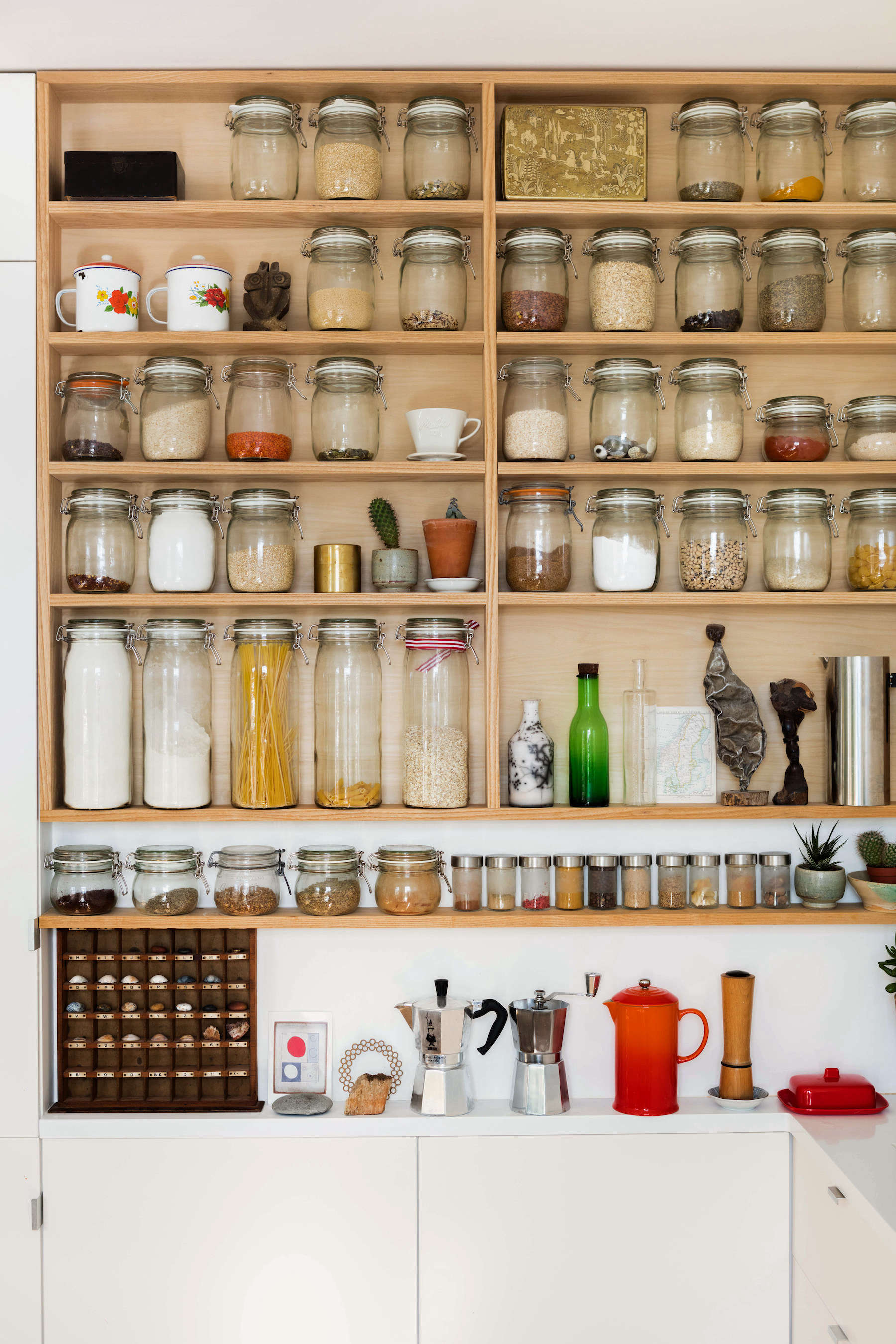 Wood pantry open shelving with decanted jars in a London apartment kitchen