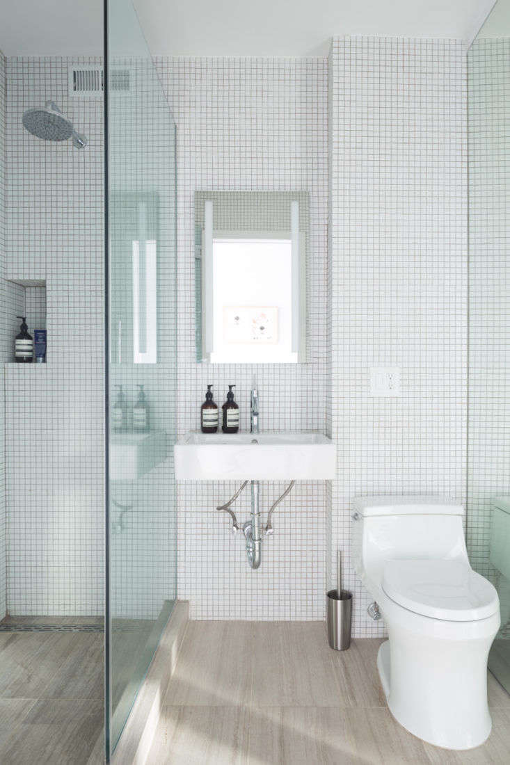 In the bathroom, an inset niche corrals shower essentials. Note also how the continuous flooring and wall tiles throughout make the room feel bigger and more cohesive.