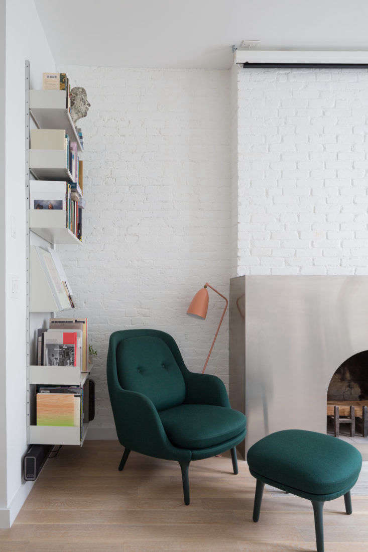 Dvir and Rauchwerger outfitted a side wall with Vitsoe shelving, which keeps books neatly corralled but still on display. (Note the periodical-style shelfin the middle that lets artful covers face outwards; see Trend Alert: 11 Periodical-Style Shelves for Design Book Lovers.) The light is the Grasshopper Floor Lamp in Salmon.