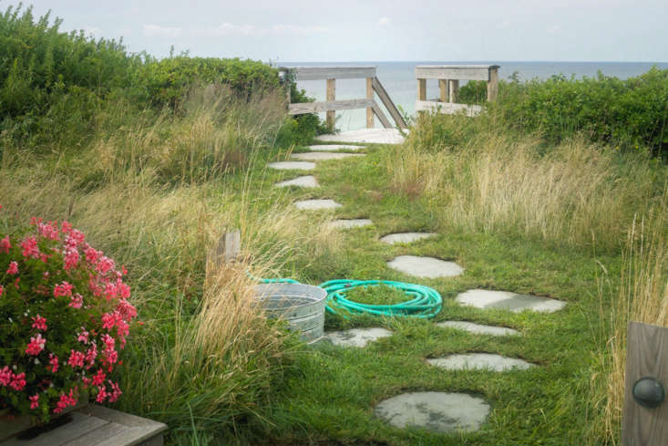 At Merryfield Cottage in Truro, Massachusetts, owners Steve Corkin and Dan Maddalena installed a convenient rinsing station, including hose and water-filled bucket, beside the beach path. SeeTales from Truro: An Untamed Landscape Channels Thoreau's Cape Cod.