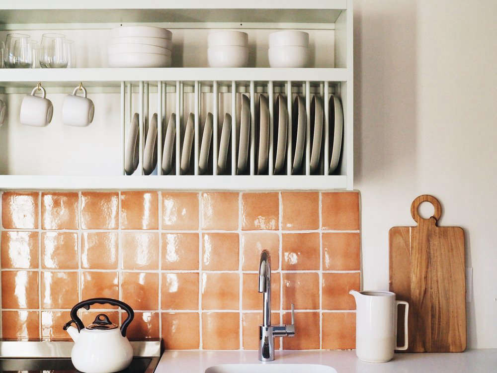 This plate rack in a small kitchenette provides a spot to dry and store dinnerware. PhotographbyMaggie Armstrong, fromThe Windrose: 9 Ideas to Steal from a Bright Apartment Hotel in Savannah.