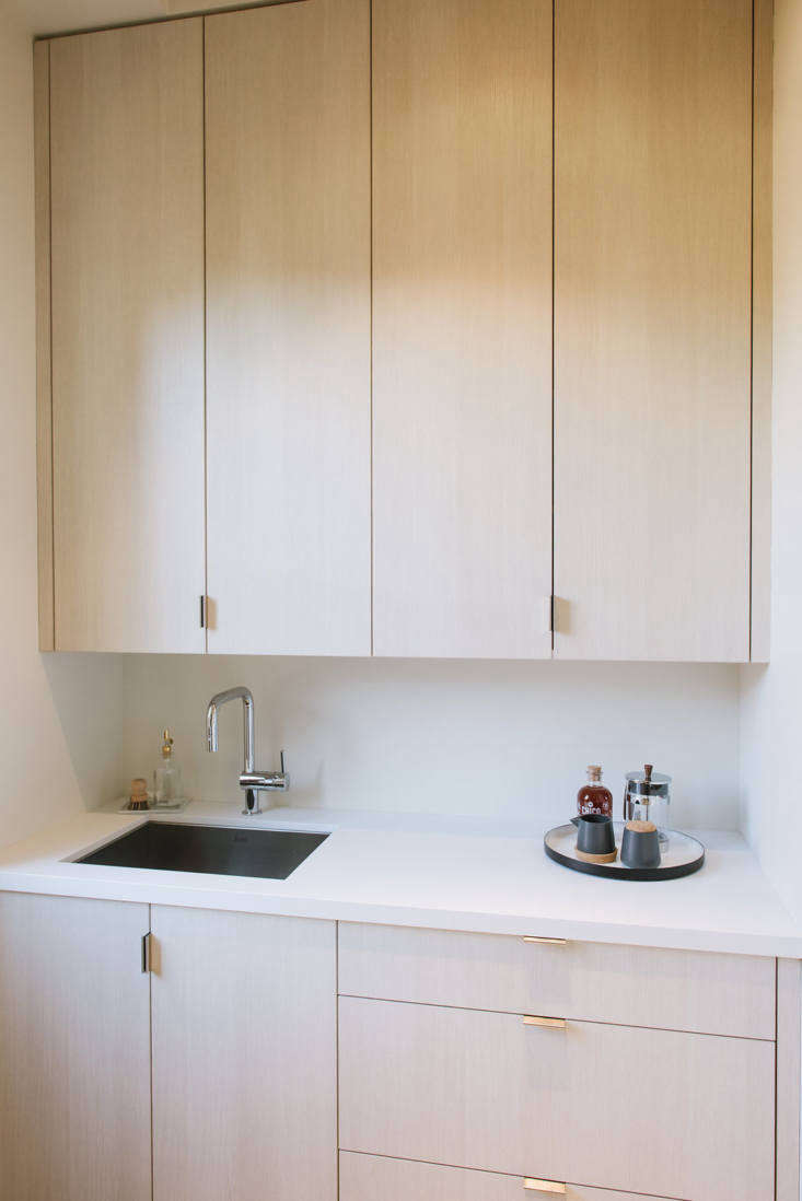 Opposite the refrigerator is closed storage (for extra dishes and small appliances) and a sink. The countertop is Caesarstone and the cabinetry is by Bachmann's husband (of Bachmann Woodworking).